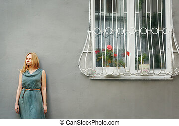 Woman in Grey Dress Standing near House