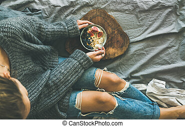 Woman in grey sweater and jeans eating rice coconut porridge...