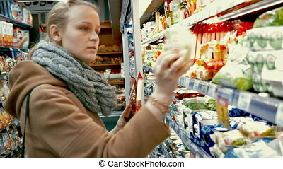Young woman in the supermarket choosing food. She examining the package of each product