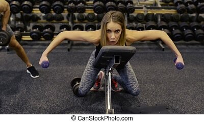 Woman in gym on bench exercising arm muscles with barbells.
