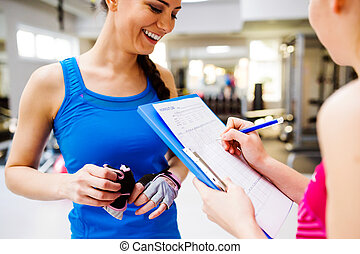 Woman in gym, personal trainer, consultiing plan on clipboard