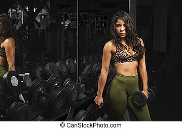 Woman in gym with dumbbell