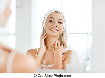woman in hairband touching her face at bathroom - beauty, ...
