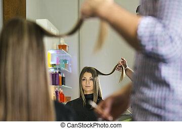 woman in hairdresser shop cutting long hair
