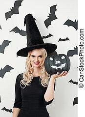 Woman in Halloween costume showing black pumpkin