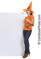 Woman in Halloween hat with blank billboard showing thumbs up