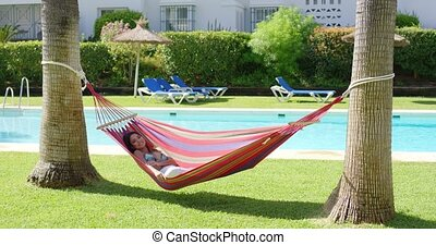 Woman in hammock at tropic resort with pool