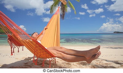 woman in hammock sideview - sideview of woman in hammock on...