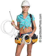 Woman in hard hat and tool belt holding coil of cable - ...