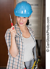 woman in hard hat showing a screw driver