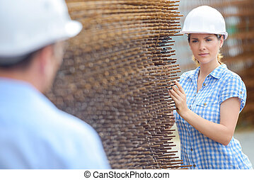Woman in hardhat next to stack of metal