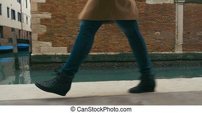 Woman in haste moving along Venetian canal
