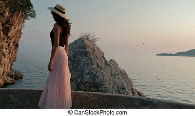 Woman in hat and pleated long skirt is walking along...