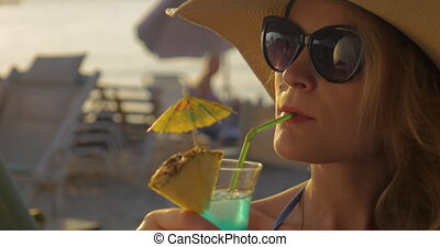 Woman in Hat and Sunglasses Drinking Cocktail