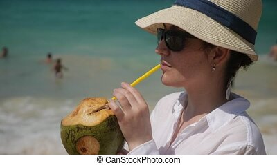 Woman in hat drinks coconut on the beach