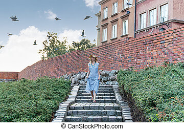 woman in hat goes down the stairs