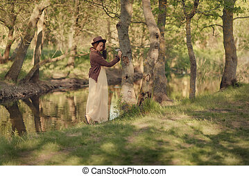 woman in hat in woods by the river