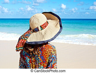 Woman in hat on the beach.