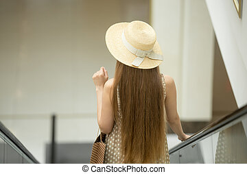 Woman in hat riding escalator in shopping mall