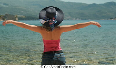 Woman in hat standing on the shore happily flinging arms to the side.