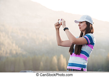 Woman in hat taking picture of a beautiful mountain landscape