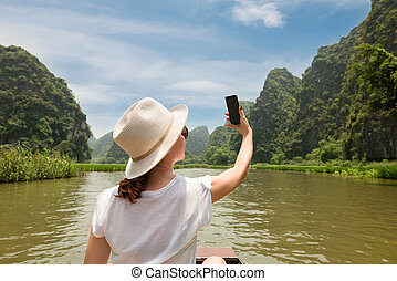 woman in hat traveling by boat among the islands and making selfie back view