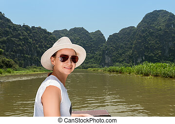 Woman in hat traveling by boat on river among the islands