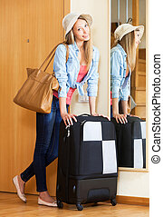 Woman in hat with a suitcase going on holidays