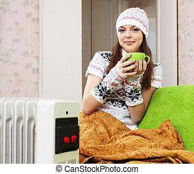 woman in hat with cup near heater