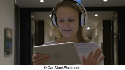 Woman in Headphondes Singing and Dancing with Tablet