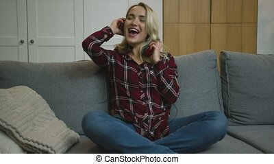 Woman in headphone having fun on sofa