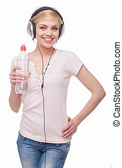Woman in headphones. Beautiful young blond hair woman in headphones holding bottle with water and smiling while isolated on white
