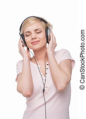 Woman in headphones. Beautiful young blond hair woman in headphones listening to the music and smiling while isolated on white