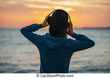 Woman in headphones enjoying sunset over the sea