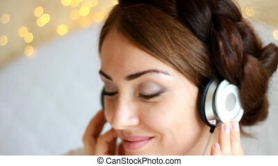 Woman in headphones listening to a music song with eyes closed.