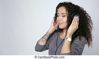 Woman in headphones listening to music dancing - Beautiful...