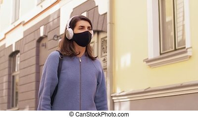 woman in headphones, mask and gloves in city - health, ...