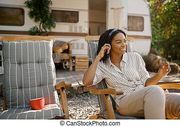 Woman in headphones near rv, camping in trailer