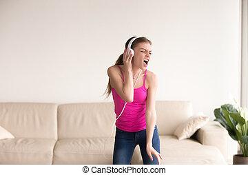 Woman in headphones singing and dancing at home