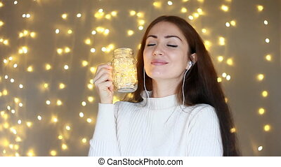 Woman in headphones smilling, listening to music, looking at...