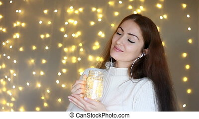 Woman in headphones smilling, listening to music, looking at the lights, closes her eyes and relaxes. Background with bokeh lights. Closeup portrait