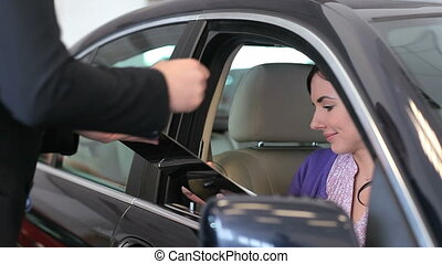 Woman in her car signing a document