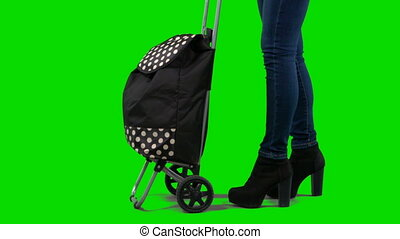Woman in high heels pulling wheeled grocery shopping bag against a green screen