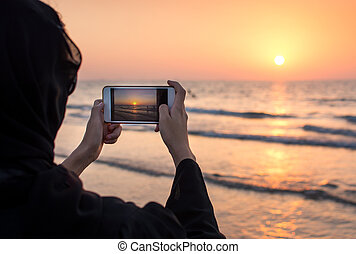 Woman in hijab taking picture of a sunset