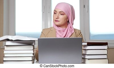 Woman in hijab typing on laptop among stacks of books