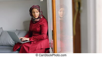 Woman in hijab using laptop in living room 4k - Woman in...