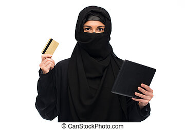 woman in hijab with tablet pc and credit card - finances,...