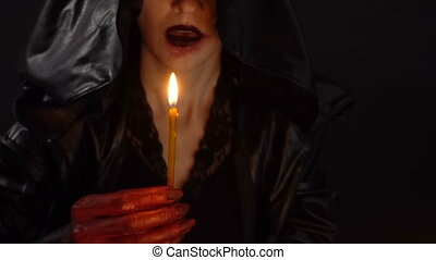 Woman in hood blow out candles