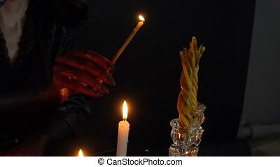 Woman in hood lights candles