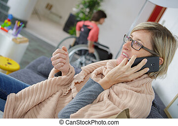 woman in hospital waiting room using her phone